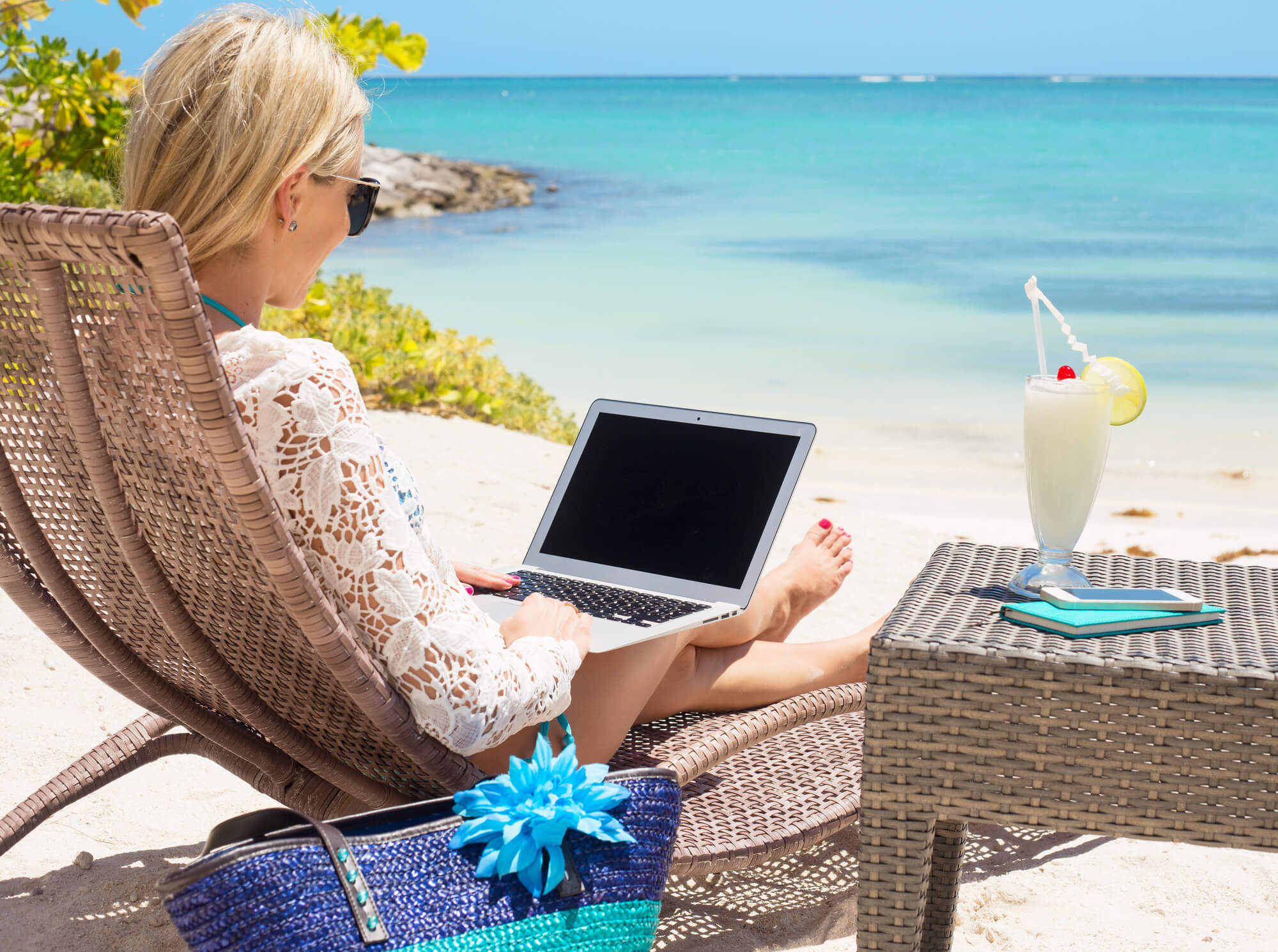 woman on beach with laptop