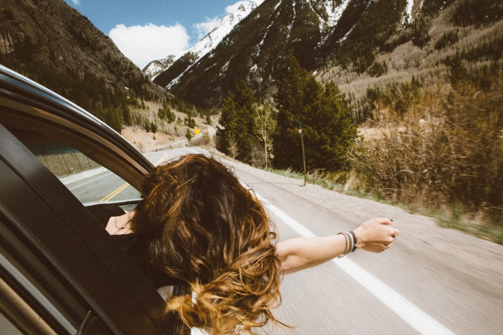Freedom woman with arm out car window