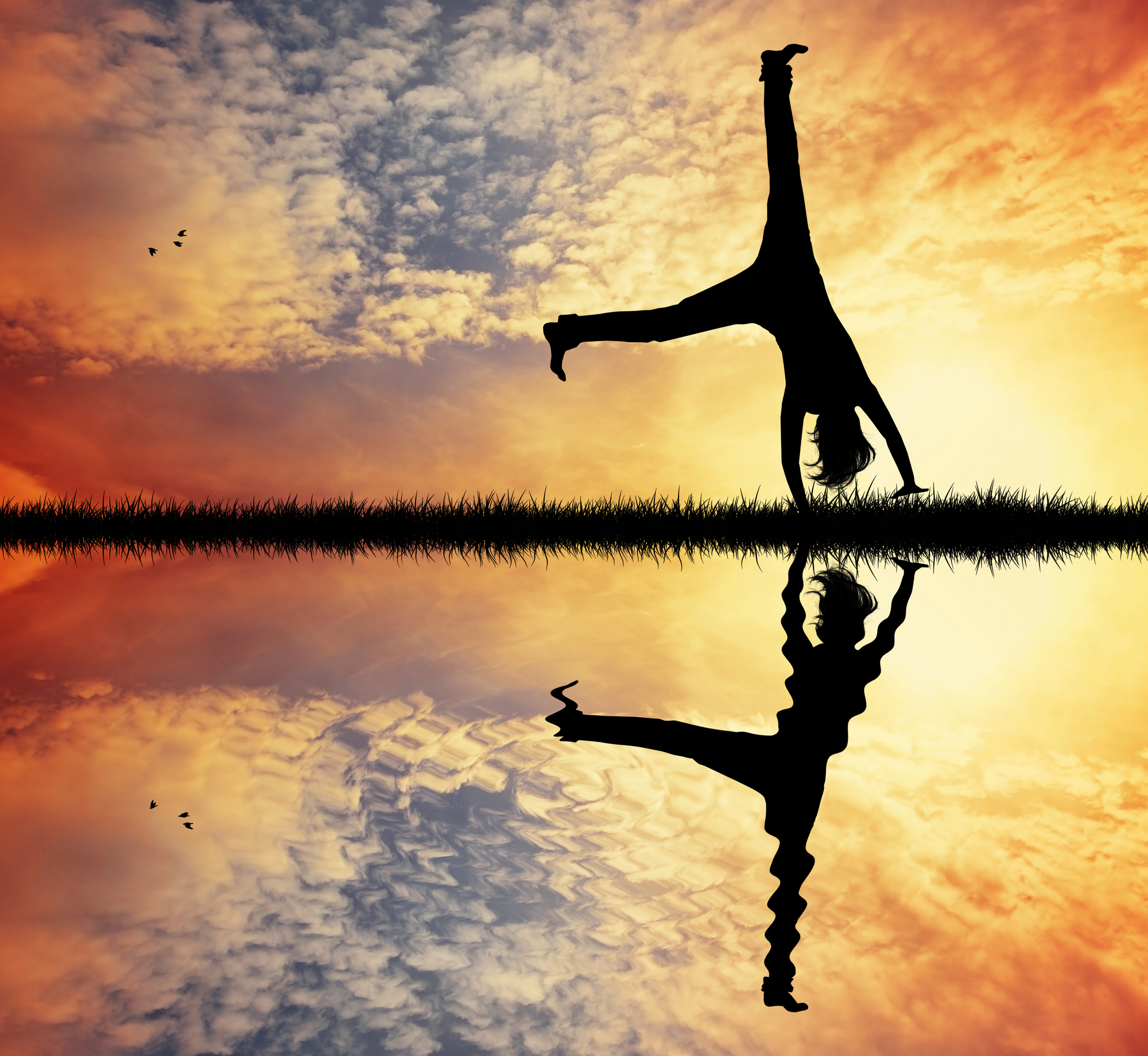Silhouette of person cartwheeling by a lake at sunrise